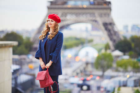 Young woman with long blond curly hair in Paris, France. Beautiful tourist in red beret near the Eiffel tower Standard-Bild - 132470421