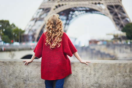 Young woman with long blond curly hair in Paris, France. Beautiful tourist in red coat near the Eiffel tower, on the Seine embankment Standard-Bild - 132470423