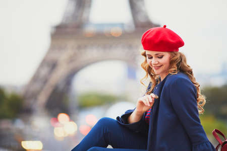 Young woman with long blond curly hair in Paris, France. Beautiful tourist in red beret near the Eiffel tower Standard-Bild - 132470431
