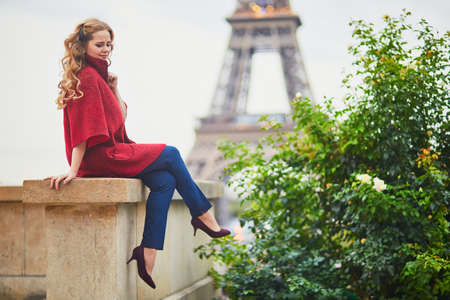 Young woman with long blond curly hair in Paris, France. Beautiful tourist in red coat near the Eiffel tower Standard-Bild - 132470441