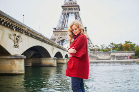 Young woman with long blond curly hair in Paris, France. Beautiful tourist in red coat near the Eiffel tower, on the Seine embankment Standard-Bild - 132470442
