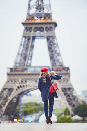 Young woman with long blond curly hair in Paris, France. Beautiful tourist in red beret near the Eiffel tower Standard-Bild - 132470449