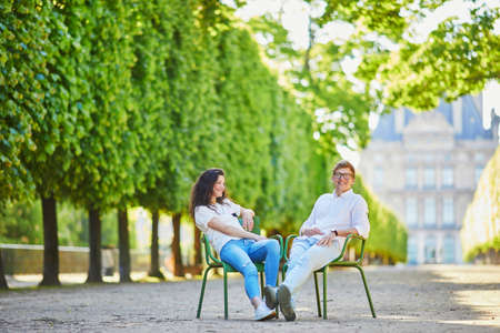 Happy romantic couple in Paris, sitting on traditional green metal chairs in Tuileries garden. Tourists spending their vacation in France Standard-Bild - 132470605