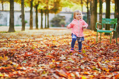 Adorable cheerful toddler girl running in Tuileries garden in Paris, France. Happy child enjoying warm and sunny fall day. Outdoor autumn activities for kids Standard-Bild - 132470611