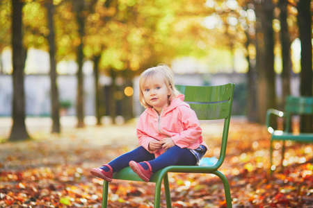 Adorable toddler girl sitting on traditional green chair in Tuileries garden in Paris, France. Happy child enjoying warm and sunny fall day. Outdoor autumn activities for kids Standard-Bild - 132470615