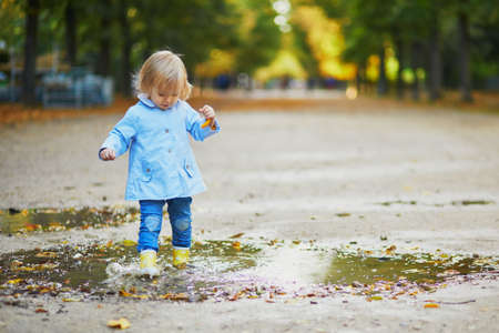 Child wearing yellow rain boots and jumping in puddle on a fall day. Adorable toddler girl having fun with water and mud in park on a rainy day. Outdoor autumn activities for kids Standard-Bild - 132198436