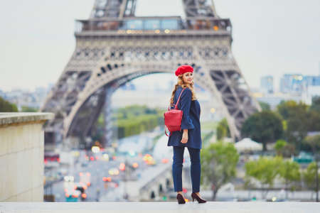 Young woman with long blond curly hair in Paris, France. Beautiful tourist in red beret near the Eiffel tower Standard-Bild - 132470619