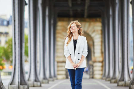 Young woman with long blond curly hair in Paris, France. Beautiful tourist in white jacket on Bir-Hakeim bridge Standard-Bild - 132470628