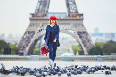 Young woman with long blond curly hair in Paris, France. Beautiful tourist in red beret near the Eiffel tower Standard-Bild - 132470629
