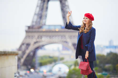 Young woman with long blond curly hair in Paris, France. Beautiful tourist in red beret near the Eiffel tower Standard-Bild - 132470631