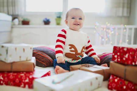 Happy little baby girl wearing warm holiday sweater opening Christmas presents on her very first Christmas. Celebrating Xmas with kids at home Stock Photo