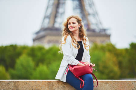 Young woman with long blond curly hair in Paris, France. Beautiful tourist in white jacket near the Eiffel tower, on the Seine embankment Standard-Bild - 132470633