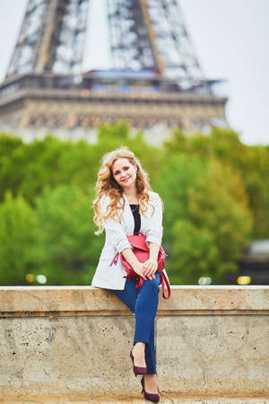 Young woman with long blond curly hair in Paris, France. Beautiful tourist in white jacket near the Eiffel tower, on the Seine embankment Standard-Bild - 132470637