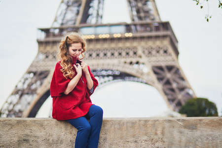 Young woman with long blond curly hair in Paris, France. Beautiful tourist in red coat near the Eiffel tower, on the Seine embankment Standard-Bild - 132470636