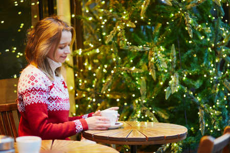 Cheerful young girl in warm red knitted holiday sweater drinking coffee or hot chocolate in cafe decorated for Christmas Standard-Bild - 132192879