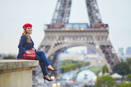Young woman with long blond curly hair in Paris, France. Beautiful tourist in red beret near the Eiffel tower Standard-Bild - 132470648