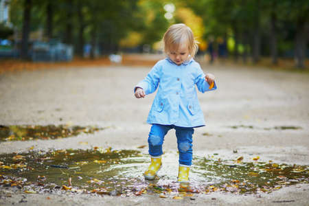 Child wearing yellow rain boots and jumping in puddle on a fall day. Adorable toddler girl having fun with water and mud in park on a rainy day. Outdoor autumn activities for kids Standard-Bild - 132193375