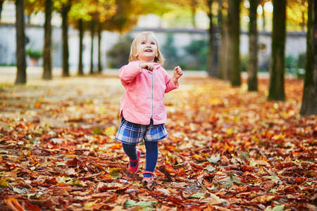 Adorable cheerful toddler girl running in Tuileries garden in Paris, France. Happy child enjoying warm and sunny fall day. Outdoor autumn activities for kids Standard-Bild - 132470651