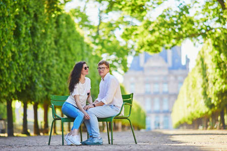 Happy romantic couple in Paris, sitting on traditional green metal chairs in Tuileries garden. Tourists spending their vacation in France Standard-Bild - 132470653