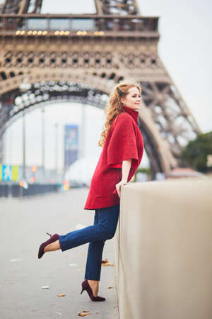 Young woman with long blond curly hair in Paris, France. Beautiful tourist in red coat near the Eiffel tower, on the Seine embankment Standard-Bild - 132470719