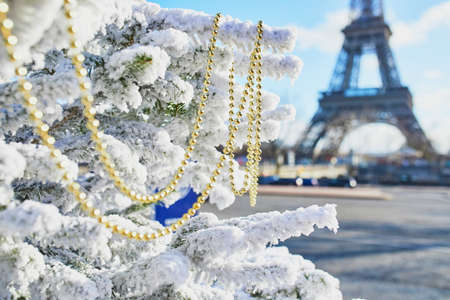 Christmas tree covered with snow and decorated with beads near the Eiffel tower in Paris. Celebrating seasonal holidays in France Standard-Bild - 132470723