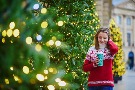 Happy young girl in warm knitted holiday sweater walking with hot drink to go on a street of Paris decorated for Christmas Stockfoto