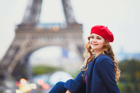 Young woman with long blond curly hair in Paris, France. Beautiful tourist in red beret near the Eiffel tower Standard-Bild - 132470733