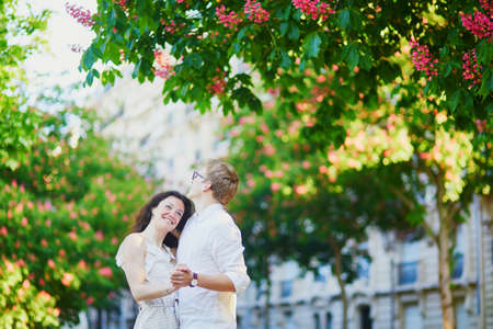 Happy romantic couple in Paris, hugging under pink chestnuts in full bloom. Tourists spending their vacation in France Standard-Bild - 132470735