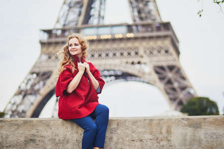Young woman with long blond curly hair in Paris, France. Beautiful tourist in red coat near the Eiffel tower, on the Seine embankment Standard-Bild - 132470739