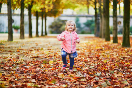 Adorable cheerful toddler girl running in Tuileries garden in Paris, France. Happy child enjoying warm and sunny fall day. Outdoor autumn activities for kids Standard-Bild - 132470741