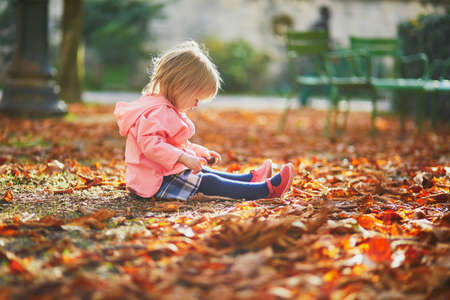 Adorable toddler girl sitting on the ground in Tuileries garden in Paris, France. Happy child enjoying warm and sunny fall day. Outdoor autumn activities for kids Standard-Bild - 132470780
