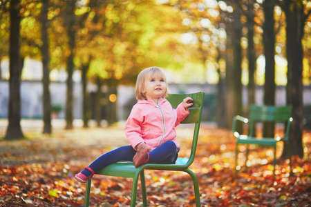 Adorable toddler girl sitting on traditional green chair in Tuileries garden in Paris, France. Happy child enjoying warm and sunny fall day. Outdoor autumn activities for kids Standard-Bild - 132470784