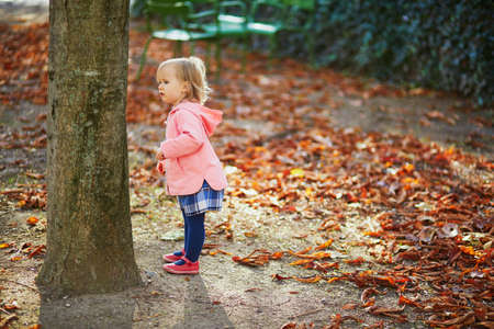 Adorable cheerful toddler girl in Tuileries garden in Paris, France. Happy child enjoying warm and sunny fall day. Outdoor autumn activities for kids Standard-Bild - 132470799