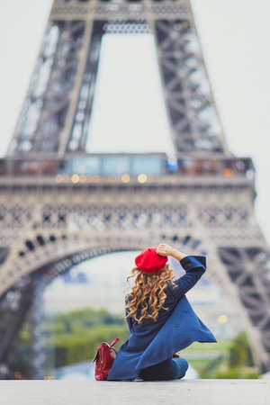 Young woman with long blond curly hair in Paris, France. Beautiful tourist in red beret near the Eiffel tower Standard-Bild - 132470819