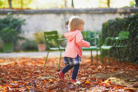 Adorable cheerful toddler girl running in Tuileries garden in Paris, France. Happy child enjoying warm and sunny fall day. Outdoor autumn activities for kids Standard-Bild - 132470879