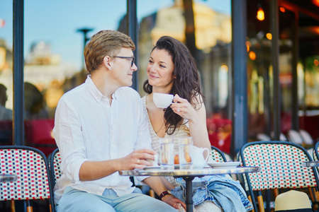 Happy romantic couple in Paris, drinking coffee in traditional Parisian outdoor cafe. Tourists spending their vacation in France Standard-Bild - 132470883