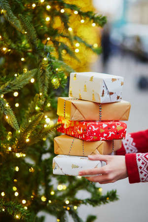 Woman hands holding pile of Christmas presents near New year tree decorated with lights and beads Standard-Bild - 132470889