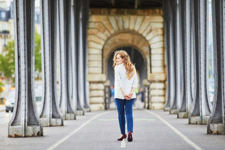 Young woman with long blond curly hair in Paris, France. Beautiful tourist in white jacket on Bir-Hakeim bridge Standard-Bild - 132470893