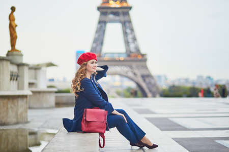 Young woman with long blond curly hair in Paris, France. Beautiful tourist in red beret near the Eiffel tower Standard-Bild - 132470894
