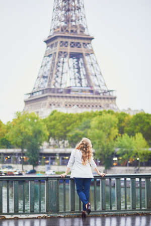 Young woman with long blond curly hair in Paris, France. Beautiful tourist in white jacket near the Eiffel tower, on the Seine embankment Standard-Bild - 132470896