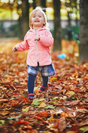 Adorable cheerful toddler girl running in Tuileries garden in Paris, France. Happy child enjoying warm and sunny fall day. Outdoor autumn activities for kids Standard-Bild - 132470898