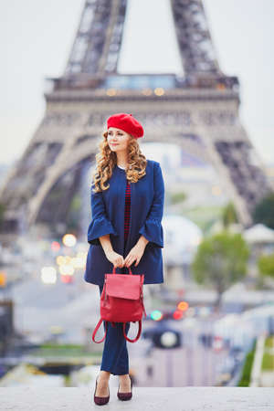 Young woman with long blond curly hair in Paris, France. Beautiful tourist in red beret near the Eiffel tower Standard-Bild - 132470900
