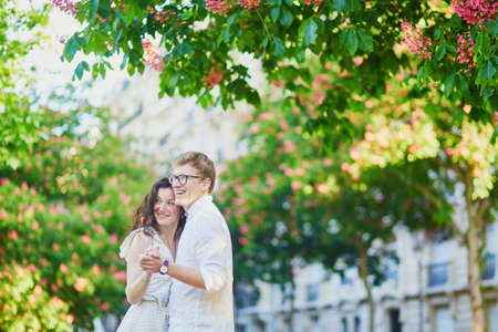 Happy romantic couple in Paris, hugging under pink chestnuts in full bloom. Tourists spending their vacation in France Standard-Bild - 132470927