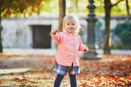 Adorable cheerful toddler girl running in Tuileries garden in Paris, France. Happy child enjoying warm and sunny fall day. Outdoor autumn activities for kids Standard-Bild - 132470932