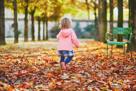Adorable cheerful toddler girl running in Tuileries garden in Paris, France. Happy child enjoying warm and sunny fall day. Outdoor autumn activities for kids Standard-Bild - 132470942