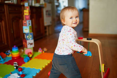 Adorable toddler girl playing with wooden toys on the floor. Happy healthy little child at home