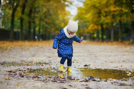 Kind trägt gelbe Regenstiefel und springt an einem Herbsttag in eine Pfütze. Entzückendes Kleinkindmädchen, das sich an einem regnerischen Tag mit Wasser und Schlamm im Park amüsiert. Outdoor-Herbstaktivitäten für Kinder