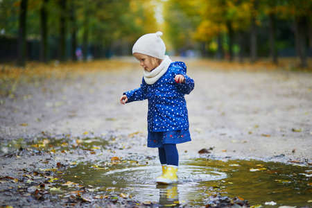 Child wearing yellow rain boots and jumping in puddle on a fall day. Adorable toddler girl having fun with water and mud in park on a rainy day. Outdoor autumn activities for kids