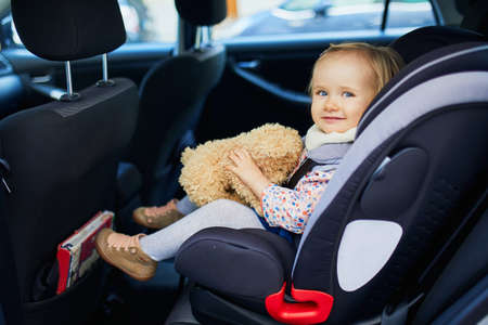 Adorable toddler girl in modern car seat with her favorite stuffed toy. Little kid traveling by car. Child safety on the road. Trip with a baby