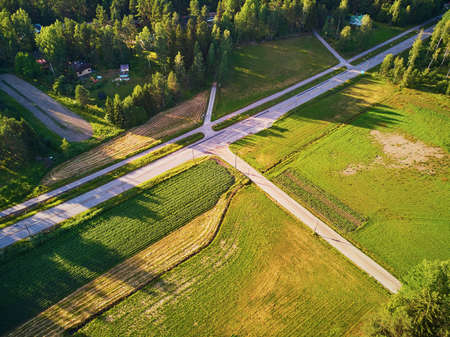 Aerial view of road surrounded by forest in typical countryside of Finland, Northern Europe